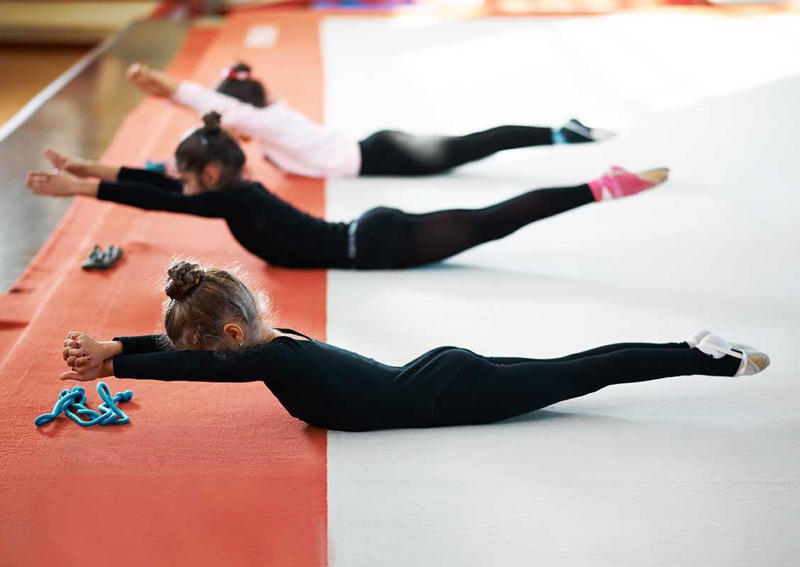Children train back exercises in a gym